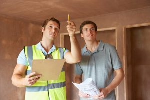 Home inspector pointing out a problem to a buyer's inspections.