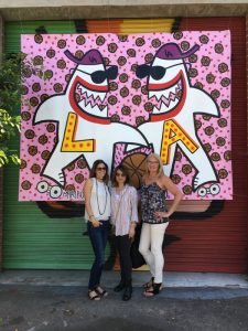 At the Brewery Art Walk, my two girlfriends and I pose in front of a large graphic art of two sharks bearing the letters LA (for Los Angeles) on their chests.
