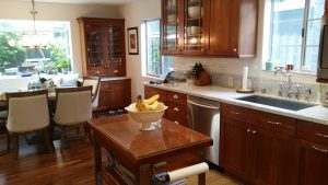 Image of the kitchen with custom cabinets of a deep rich wood and small island.