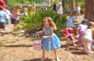 In the South, Bay, a young girl holding an easter basket runs around the park looking for easter eggs. More kids in the background.