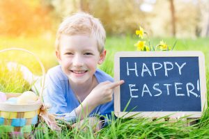Young boy in the South Bay sprawled out in the grass with a big smile on his face pointing to his Happy Easter sign on a chalk board.
