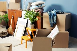 An image of boxes stacked up along with a plant, chair and some pillows. A rent-back gives a seller more time to move.
