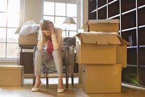 A woman sits in a chair with her head in her hands. There are boxes all around her. She is exhausted and frustrated with moving. A rent-back agreement would give her more time to move.